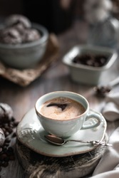 A cup of coffee with coffee beans and chocolate chip cookie on a beautiful brown background. Dark