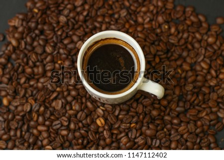 A cup of coffee with coffee beans on a dark background. A delicious fragrant coffee of the best varieties.