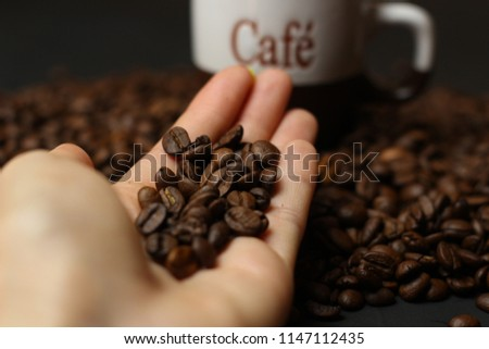 A cup of coffee with coffee beans on hand on  a dark background. A delicious fragrant coffee of the best varieties.