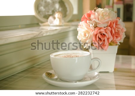 A cup of coffee with flower in vintage cafe