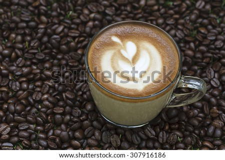 A cup of coffee with flower shape milk foam on coffee bean background