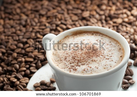 A Cup of Coffee with Foam and Cinnamon on top of Coffee Beans with Scattered Beans on Plate
