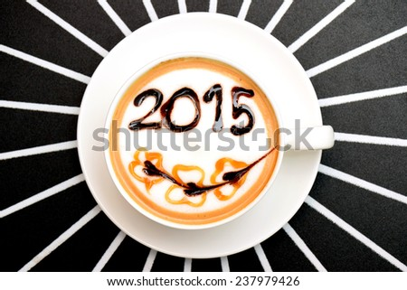 A cup of coffee with foam milk art 2015 pattern in a white cup on white line and black background