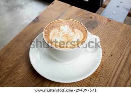 A cup of coffee with leaf pattern in a white cup on wooden background.