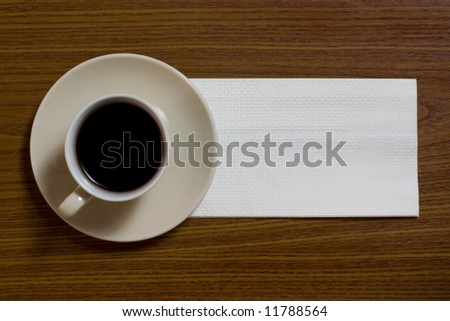 A cup of coffee with napkin on a table