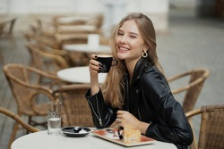 a Cup of delicious aromatic hot coffee is held in the hands of a charming confident blonde woman of Caucasian appearance ethnic. Breakfast cakes and a bottle of water on the table, summer cafe