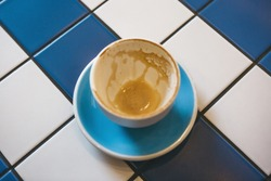 A cup of drunk coffee on a ceramic tile table. Concept for completing a meeting or coffee break.
