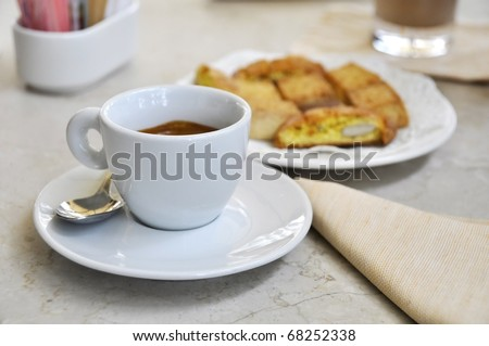 A cup of espresso coffee and biscuits on a marble table