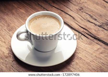 a cup of espresso on grunge wooden background