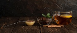 A Cup of fragrant black tea with lemon and cinnamon and milk chocolate with mint and honey on a natural background. The concept of relaxation, eating.