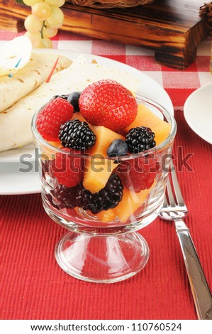 A cup of fresh berries, cantaloupe and ham and egg burritos