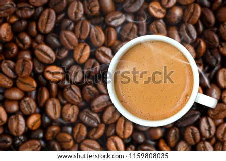 A cup of fresh coffee top view with smoke on coffee beans background, shallow dept of field. Coffee cup on blurred coffee beans #1159808035