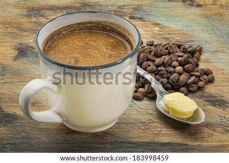 a cup of fresh fatty coffee with butter and coconut oil - ketogenic diet concept - stock photo