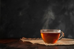 A Cup of freshly brewed black tea,escaping steam,warm soft light, darker background.