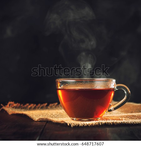 A Cup of freshly brewed black tea,escaping steam,warm soft light, darker background. #648717607