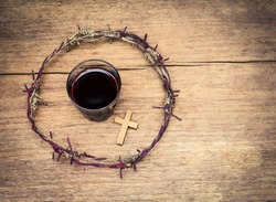 a cup of grape juice with wooden cross and  metal Barbed Wire made like the crown of thorns of Jesus on wooden background, Christian concept, Easter background with copy space