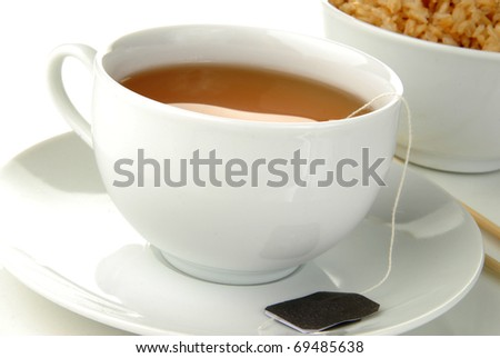 A cup of green tea by a bowl of rice