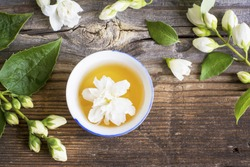 A cup of green tea infused with jasmine on a gray wooden background. selective focus