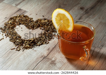 A cup of green tea standing on a wooden table. Next to a cup of heart made of dried green tea leaves