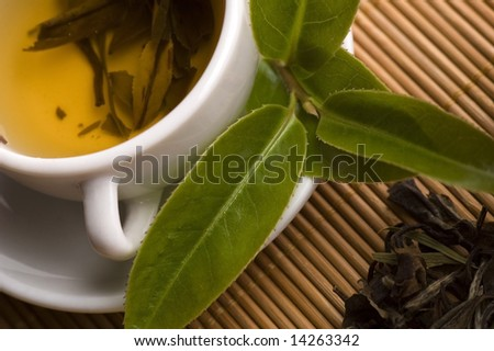 a cup of green tea with freh leaves on the bamboo tray