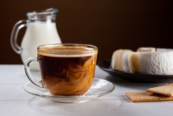 A cup of hot american black coffee with cream poured over. Tasty breackfast with creamy Camembert cheese on natural white wooden table.