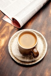 A cup of hot black morning coffee with a vintage wooden table. A close up of americano or double espresso. Coffee break.