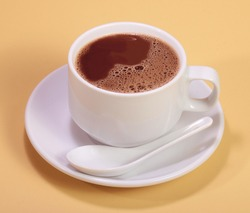 A cup of hot chocolate drink on simple yellow background