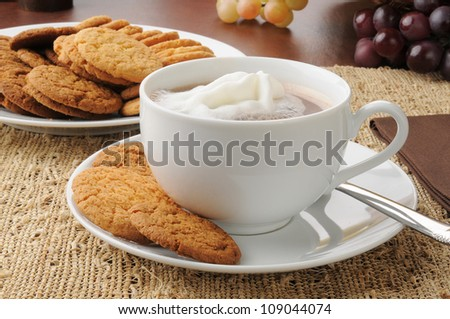 A cup of hot chocolate or cappuccino with ginger and lemon snap cookies