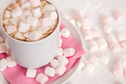 a Cup of hot cocoa with marshmallows on a pink napkin of plate.Cup there's on white patterned tablecloth .