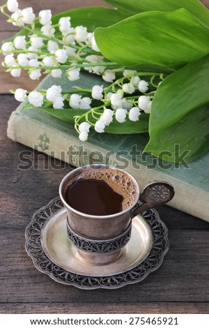 A cup of hot coffee, a bouquet of lilies of the valley, the old book