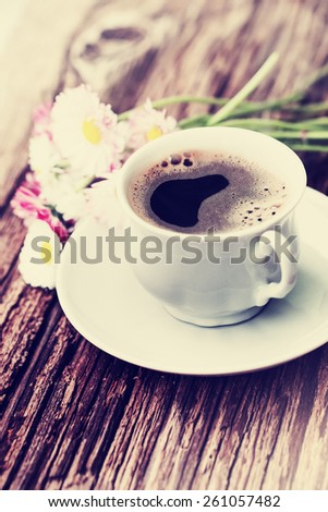 A cup of hot coffee and flowers/ Romantic background with retro filter effect