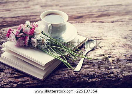 A cup of hot coffee, flowers and book. Romantic background with retro filter effect