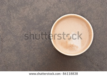 a cup of hot coffee in paper cup taken from the top view with creamy milk inside