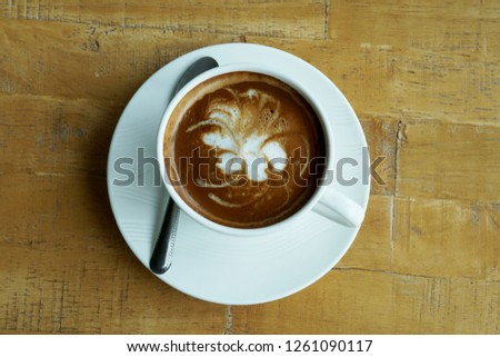 A cup of hot latte art coffee on wooden table #1261090117