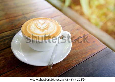 A Cup of hot latte art coffee on wooden table