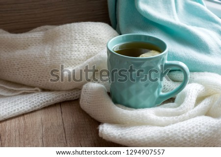 A cup of hot tea with lemon. Still life with warm scarf and blue cup on a wooden table. Winter, or autumn mood concept. Warm autumn or winter picture. Selective focus. At home. Warming. Good morning.