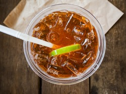 A cup of ice lemon tea on wooden table, top view