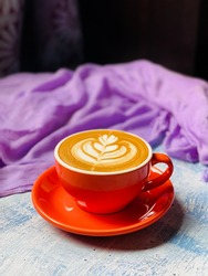 A cup of latte with tulip latte art on rastic table top
