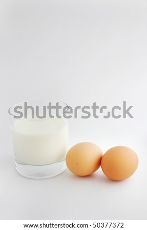 A cup of milk with two eggs.