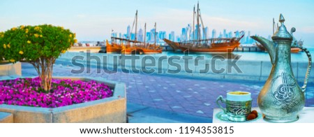 A cup of refreshing coffee, brewed in vintage dallah coffeepot, decorated with Islamic patterns, with a view on Doha harbor full of dhow boats and skyscrapers behind the waters of Persian Gulf, Qatar. - Shutterstock ID 1194353815