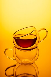 A cup of strong tea in empty cup flooded with yellow-gold light