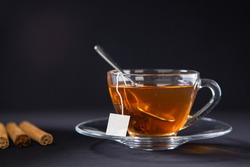 A cup of tea, Cinnamon tea, Cinnamon drink with cinnamon stick on a Tea Bag, leaf on a Black background, Spoon, Transparent cup, Ceylon Tea, Sri lanka, Ceylon Cinnamon