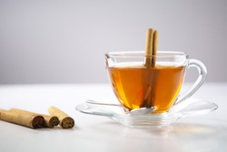 A cup of tea, Cinnamon tea, Cinnamon drink with cinnamon stick on a Tea Bag, leaf on a white background, Spoon, Transparent cup, Ceylon Tea, Sri lanka, Ceylon Cinnamon