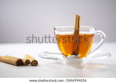A cup of tea, Cinnamon tea, Cinnamon drink with cinnamon stick on a Tea Bag, leaf on a white background, Spoon, Transparent cup, Ceylon Tea, Sri lanka, Ceylon Cinnamon