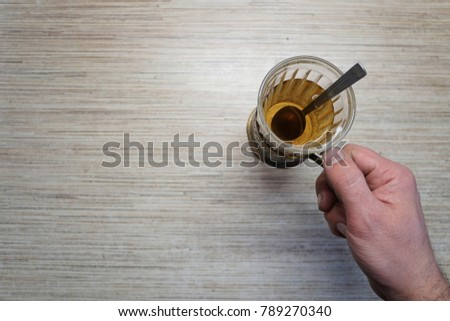A Cup of tea in a glass beaker. The view from the top. The wooden table. One object. The hand of man. The cozy atmosphere. Design element