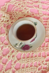 A cup of tea in the morning with doily crochet background. Selective focus.