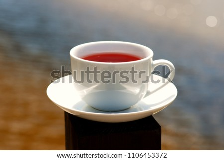 A cup of tea on vacation. Relax on the river bank in spring and summer with a cup of tea. A cup of tea, a river with blue and yellow shades, sunny glare is beautiful. #1106453372