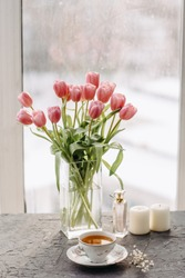 a Cup of tea, perfume, bouquet of tulips, candles, on a gray table by the window
