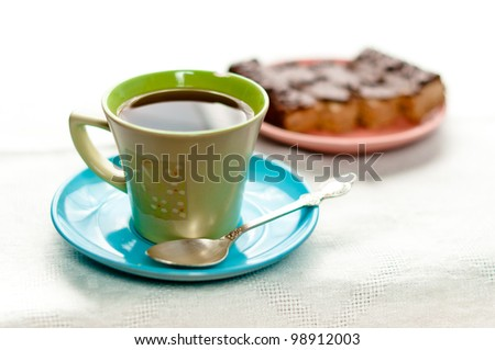 A cup of tea standing on table with small pie part on background