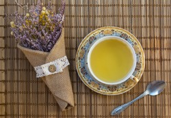 A cup of tea with a beautiful vintage bouquet of dried flowers on wicker cloth. Horizontal top view